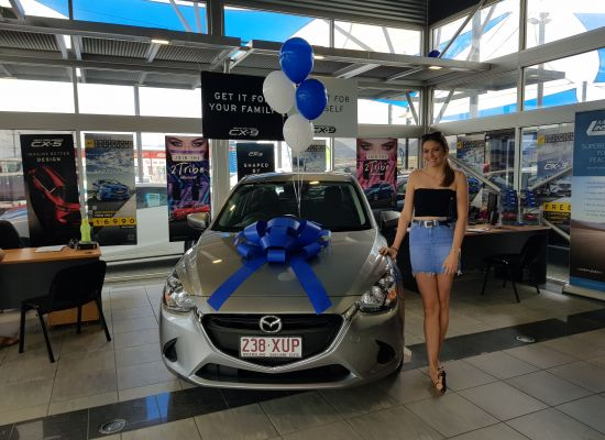 Kaelin taking delivery of a Mazda Mazda 2